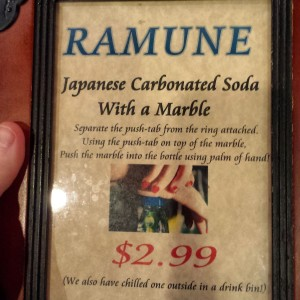 Ramune Sign at Epcot Japan, advertising soda sealed with a marble and opened by pushing the marble down breaking the seal.