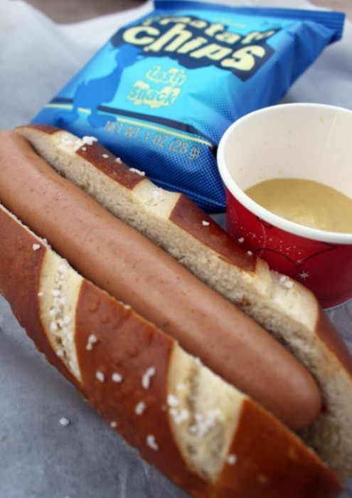 Frankfurter in a pretzel roll served with chips and Dijon mustard