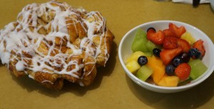 "The ""appetizer"" is a massive cinnamon roll bake and a large dish of fruit. Photo by Julia Mascardo"