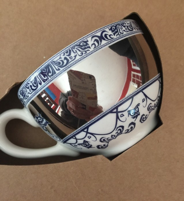 The teacup is highly reflective. That's me trying to take of photo of it with my phone.