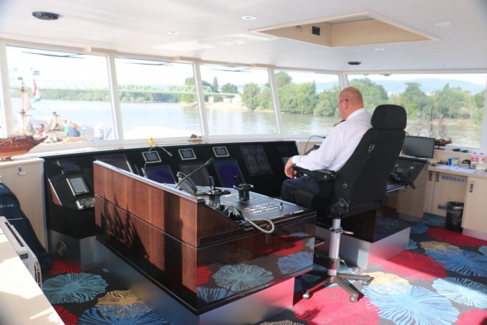 The captain on the Navigation Bridge. Guests are often able to join the captain to learn more about the ship.