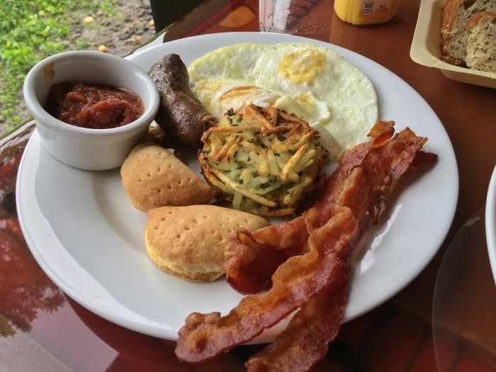 Boere Breakfast with cage-free eggs cooked to order, tomato chutney, boerewors sausage, bacon, Tanzanian hash browns, and coconut Johnny cakes