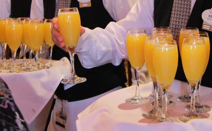 Trays of mimosas are quickly emptied as guests enter the Parisian Breakfast