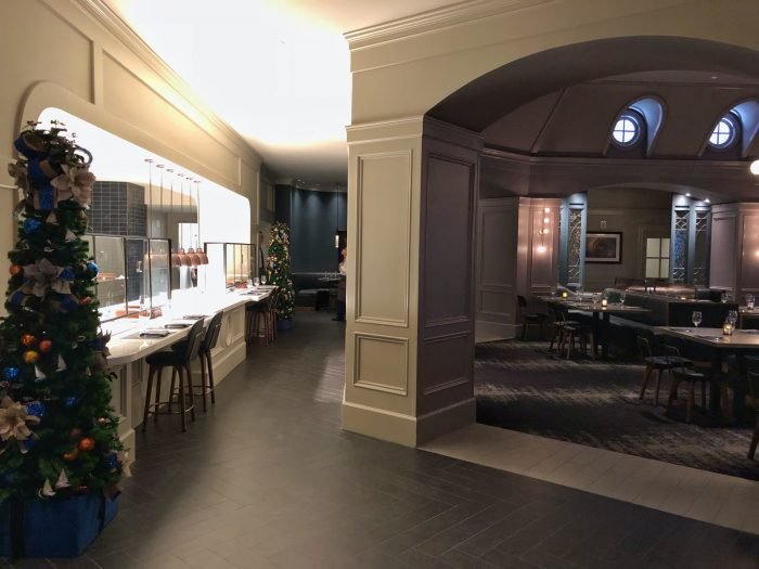 The interior of Ale & Compass as you first arrive at the restaurant is bathed in muted greys and blues.